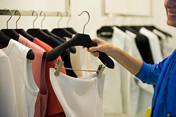 Femme tenant un vêtement devant une rangée de supports.